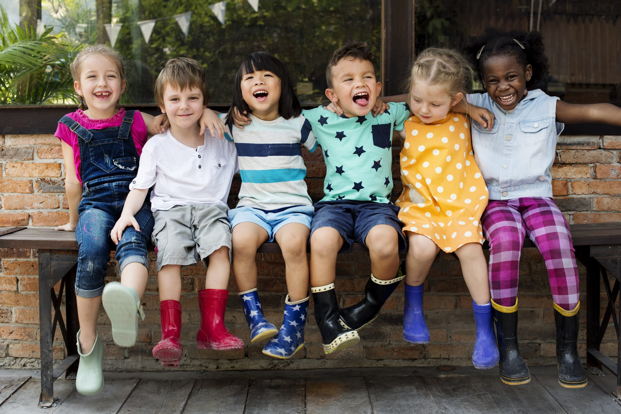 smiling children arm in arm outside on bench